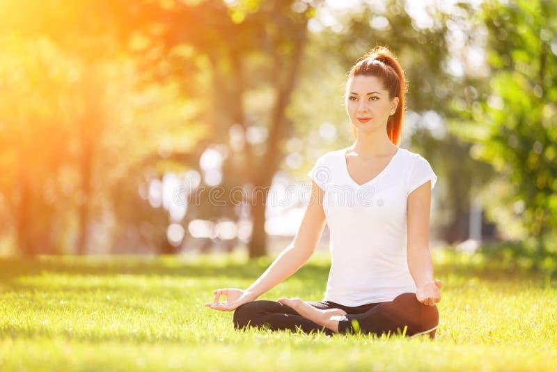 Yoga openlucht De gelukkige vrouw die yogaoefeningen doen, mediteert royalty-vrije stock afbeeldingen