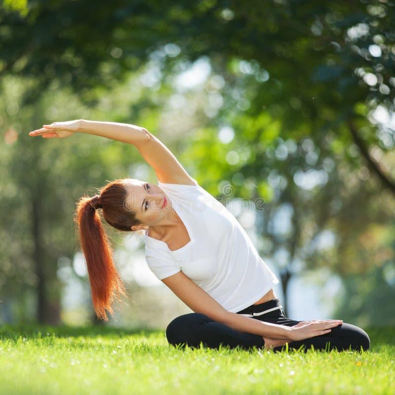 Yoga openlucht De gelukkige vrouw die yogaoefeningen doen, mediteert in stock foto