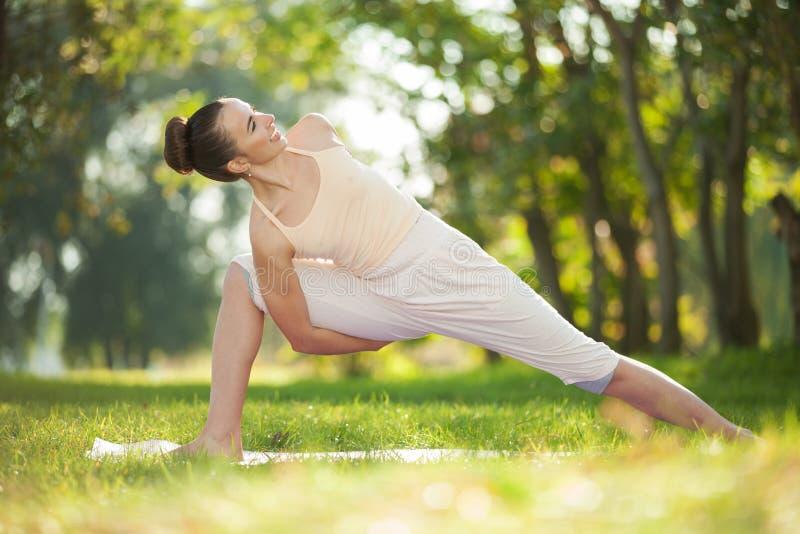 Yoga openlucht De gelukkige vrouw die yogaoefeningen doen, mediteert in het park Yogameditatie in aard Concept gezonde levensstij royalty-vrije stock afbeeldingen