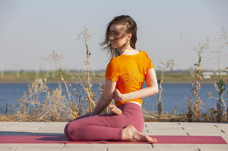 Yoga openlucht De gelukkige vrouw die yogaoefeningen doen, mediteert in het park Yogameditatie in aard Concept gezonde levensstij stock afbeeldingen