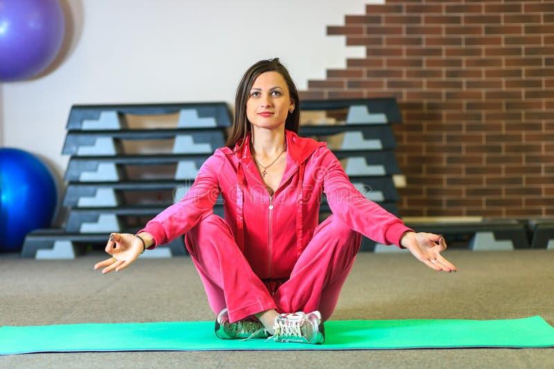 Yoga opleiding Het mooie witte meisje in een roze sportenkostuum mediteert op de yogaklasse op het fitness centrum stock afbeeldingen