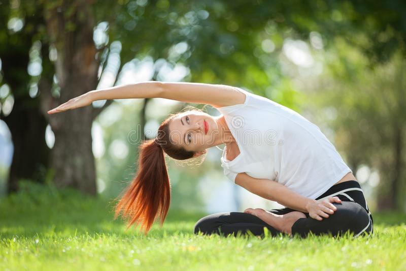 Yoga outdoor. Happy woman doing yoga exercises, meditate in the park. Yoga meditation in nature. Concept of healthy lifestyle stock photography