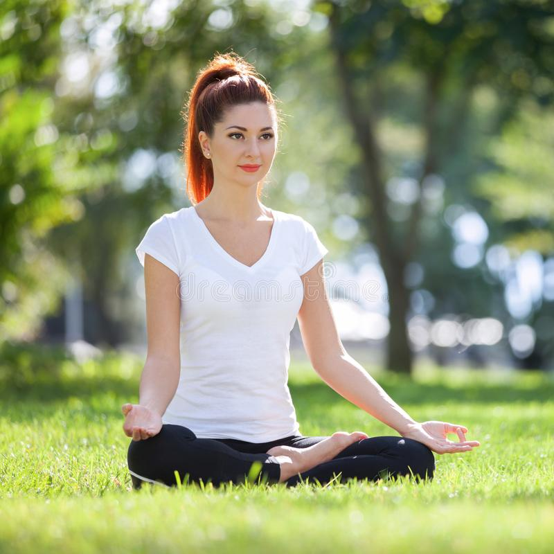 Yoga outdoor. Happy woman doing yoga exercises, meditate in the park. Yoga meditation in nature. Concept of healthy lifestyle and royalty free stock photography