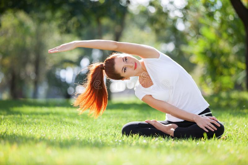 Yoga outdoor. Happy woman doing yoga exercises, meditate in the park. Yoga meditation in nature. Concept of healthy lifestyle royalty free stock photos