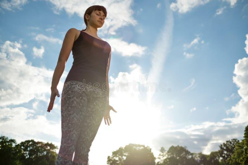 Yoga outdoor in park. Woman doing yoga exercises.Mountain yoga pose tadasana. Yoga outdoor. Woman doing yoga exercises on the red mat, meditate in the park on stock photo