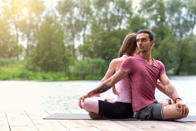 Yoga outdoors. Family couple exercising. Concept of healthy lifestyle royalty free stock images