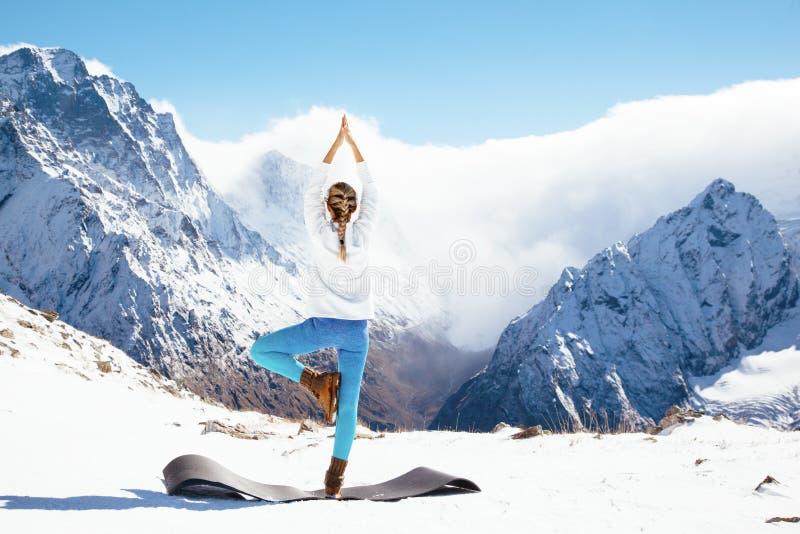 Yoga på berget i vinter royaltyfri foto