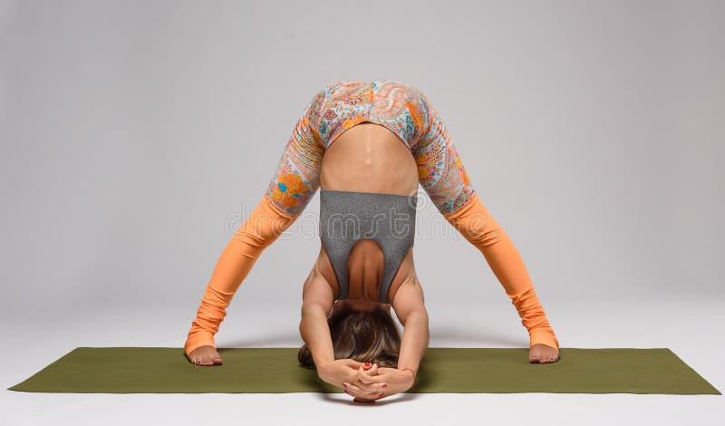 Yoga på mattt i studio royaltyfri fotografi