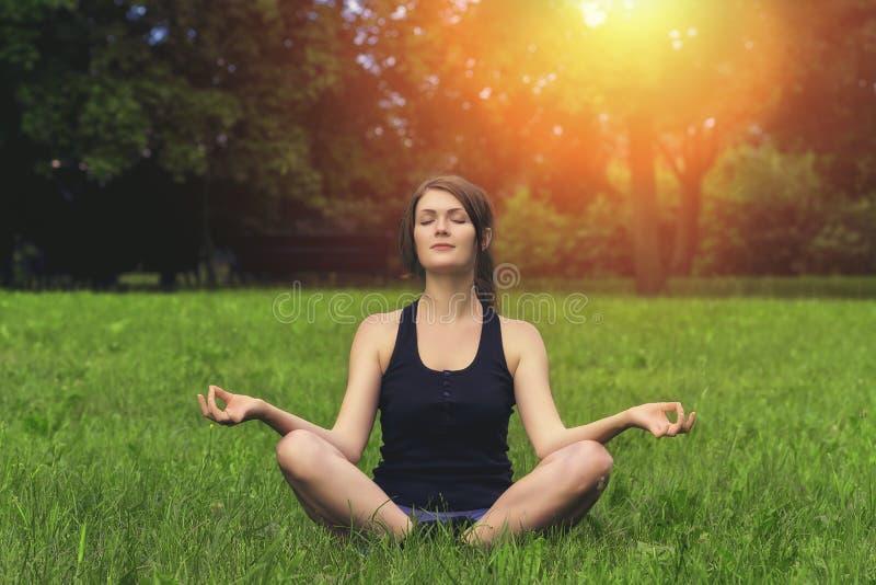 Yoga på solnedgången i parkera arkivfoton