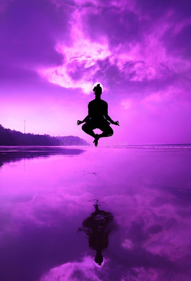 Yoga padmasana in jumping on the beach stock photography