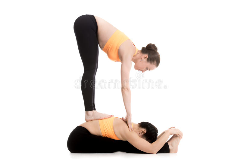 Yoga with partner, seated and standing forward bend stock photo