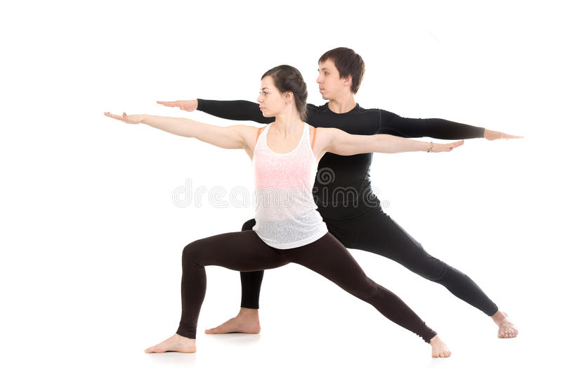 Yoga with partner, Virabhadrasana 2. Two sporty people practice yoga with partner, doing lunge exercise, Warrior II posture, Virabhadrasana 2, side view royalty free stock photography