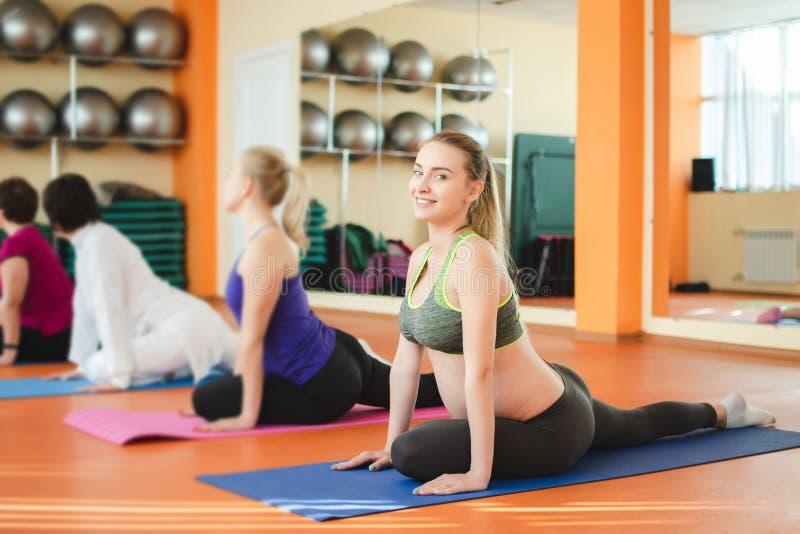 Yoga per le donne incinte Giovane bella ragazza incinta in abiti sportivi che fanno yoga nella palestra fotografia stock