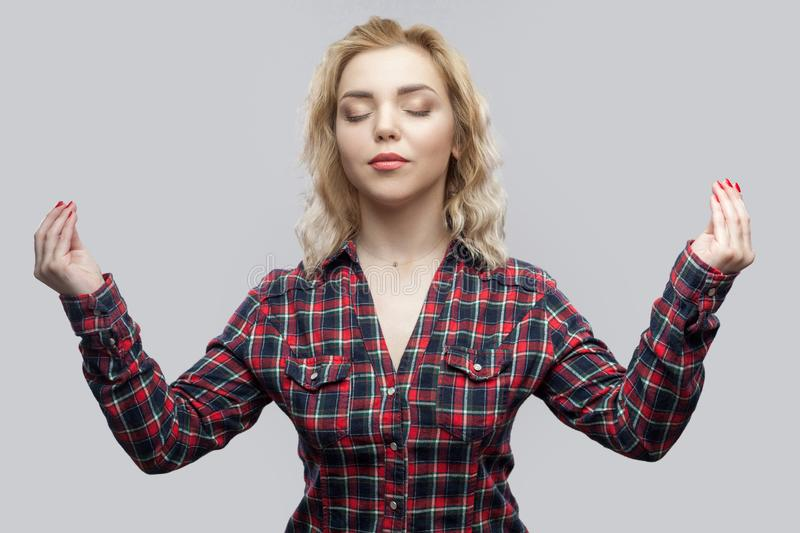 Yoga. Portrait of calm beautiful blonde young woman in casual red checkered shirt standing with crossed arms, smiling, closed eyes royalty free stock image
