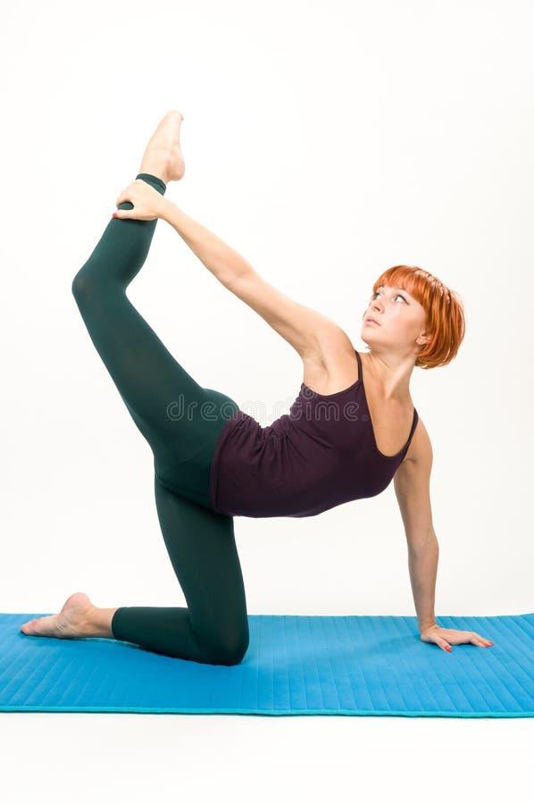 Yoga posant sur un fond gris de studio images stock