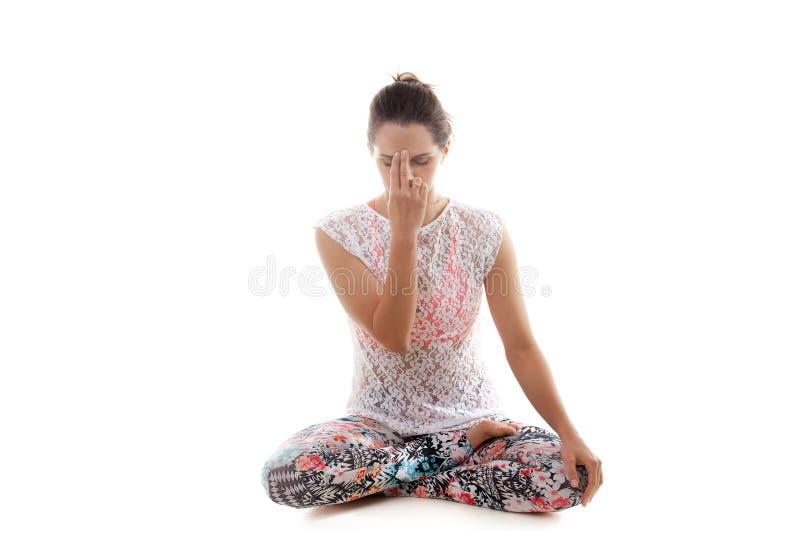 Yoga Pose nadi shodhana pranayama. Yoga girl on white background practicing nadi shodhana pranayama (Alternate, Nostril, Breathing royalty free stock photography