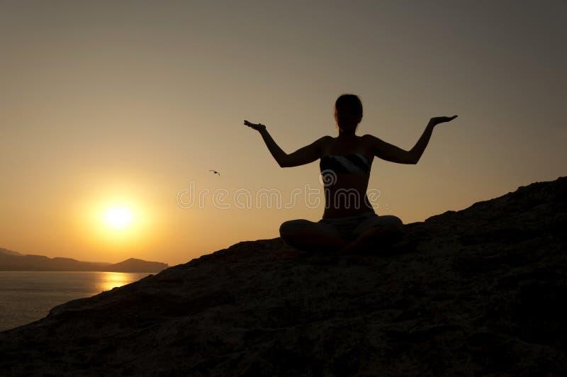 Yoga pose silhouette at sunrise royalty free stock image