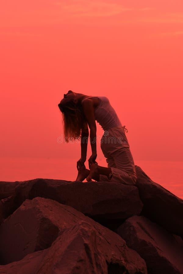 Yoga poserar på solnedgången på stranden royaltyfri foto