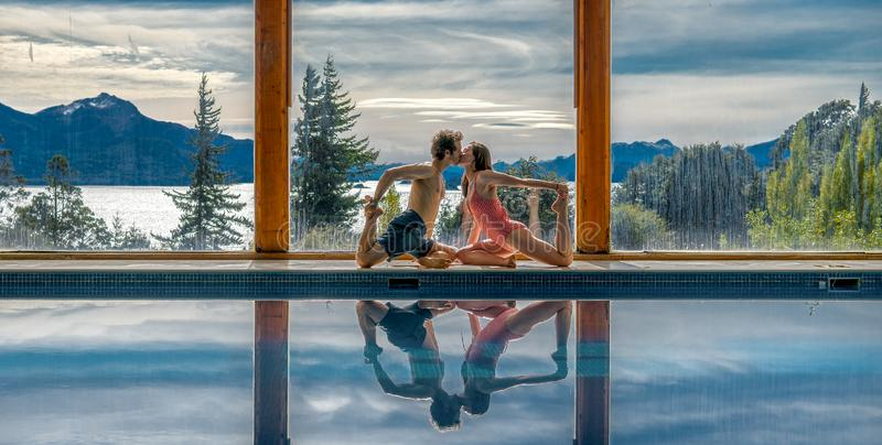 Yoga Poses by Pool. Infront of mountains and lake with reflection in pool, family, landscape, nature, outdoors, sunset, adult, asana, ashtanga, beautiful, blue royalty free stock photos