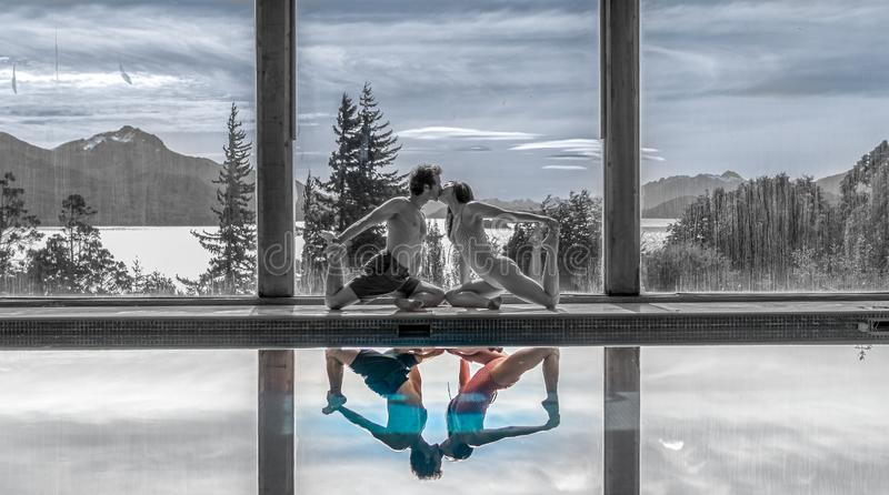 Yoga Poses by Pool. Infront of mountains and lake with reflection in pool, family, landscape, nature, outdoors, sunset, adult, asana, ashtanga, beautiful, blue royalty free stock photo