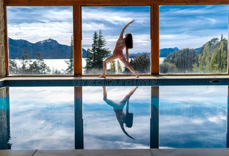 Yoga Poses by Pool. Infront of mountains and lake with reflection in pool, landscape, nature, outdoors, adult, ashtanga, beautiful, blue, body, concentration royalty free stock image
