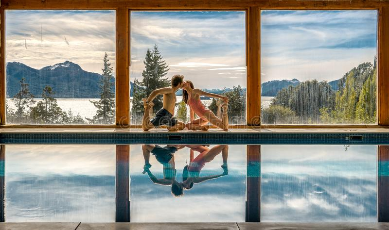 Yoga Poses by Pool. Infront of mountains and lake with reflection in pool, family, landscape, nature, outdoors, sunset, adult, asana, ashtanga, beautiful, blue royalty free stock photography