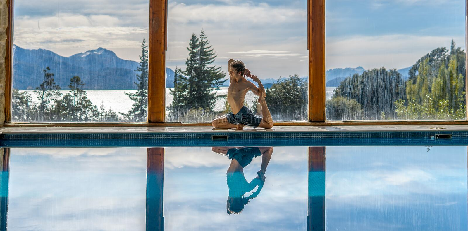 Yoga Poses by Pool. Infront of mountains and lake with reflection in pool, landscape, nature, active, adult, arm, asana, body, concentration, exercise, fit royalty free stock photo