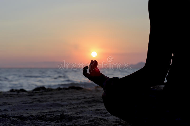 Yoga posture backlight. Backlight of a woman practicing yoga sitting on the seashore at sunset simulating holding the sun in her finger - focus on the fingers stock photo