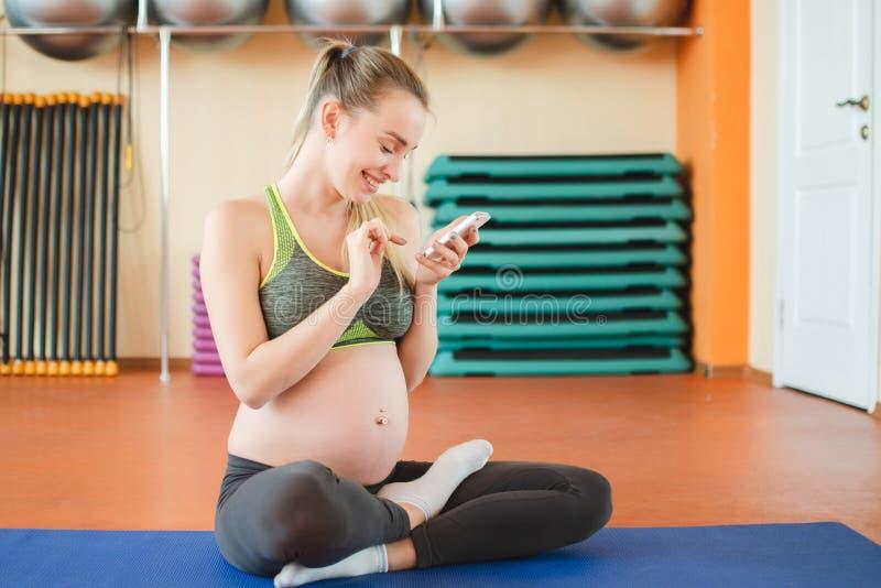Yoga pour les femmes enceintes Jeune fille enceinte faisant le yoga photographie stock libre de droits