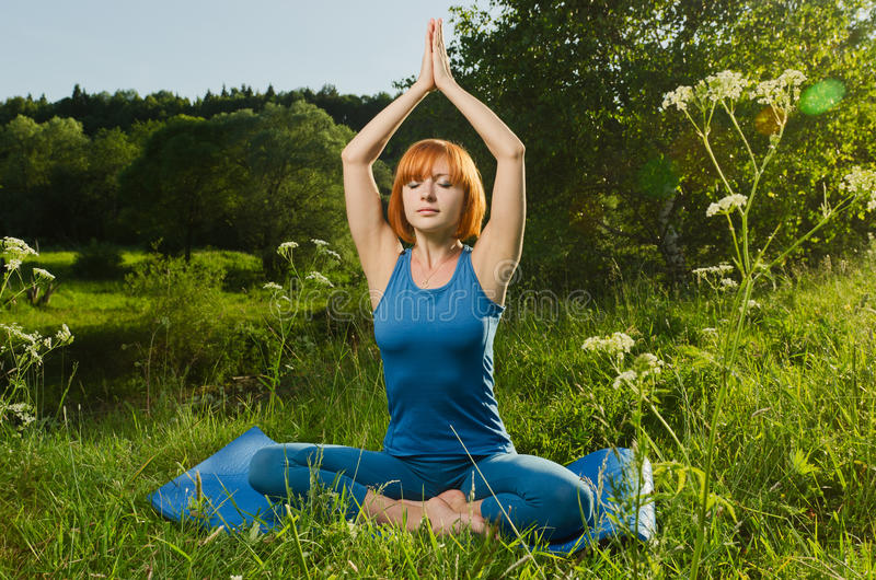 Yoga practicante de la aptitud de la mujer roja imágenes de archivo libres de regalías