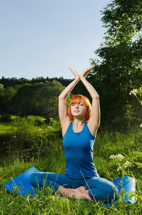 Yoga practicante de la aptitud de la mujer roja foto de archivo