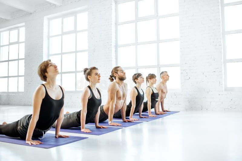 Yoga practicante de la gente en el estudio imagen de archivo