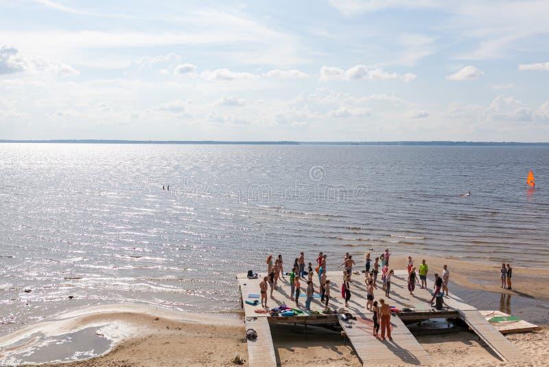 Yoga practicante de la gente en la playa imagen de archivo