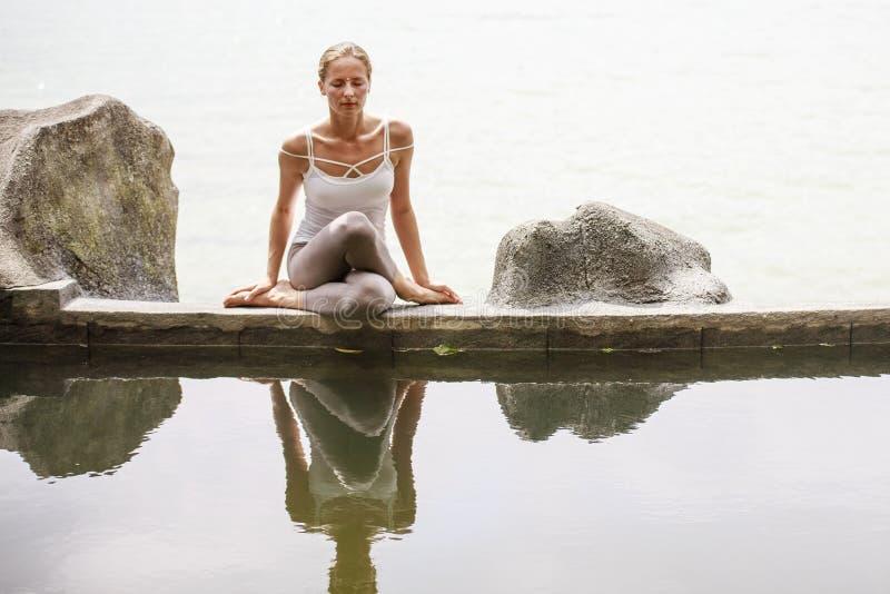 Yoga practicante de la meditación de la mañana de la mujer en la playa foto de archivo