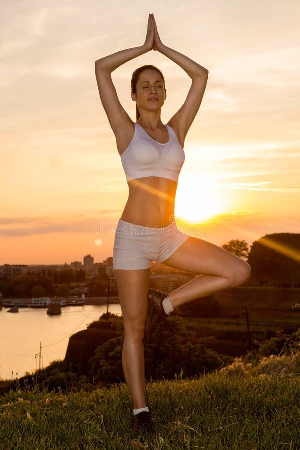 Yoga practicante de la muchacha hermosa en puesta del sol foto de archivo libre de regalías
