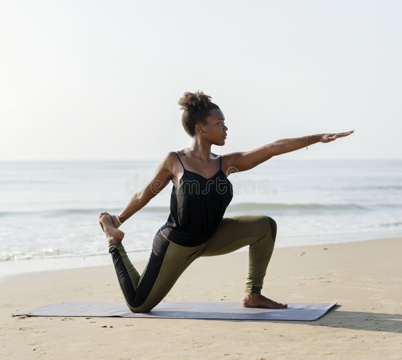 Yoga practicante de la mujer afroamericana en la playa foto de archivo