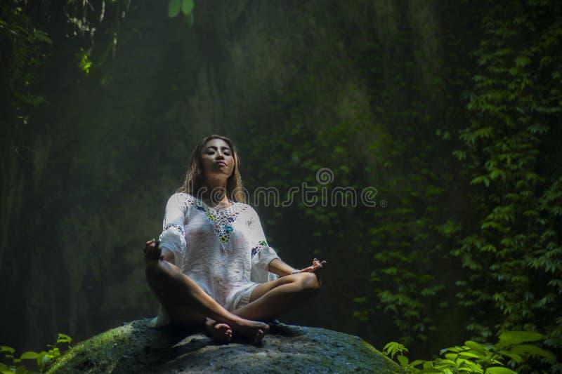 Yoga practicante de la mujer asiática hermosa joven que plantea sentarse en la posición de loto que medita sobre una piedra en un foto de archivo
