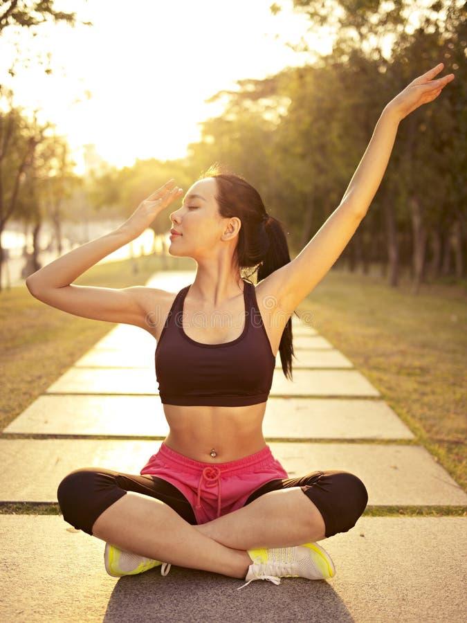 Yoga practicante de la mujer asiática joven al aire libre en la puesta del sol imagen de archivo libre de regalías