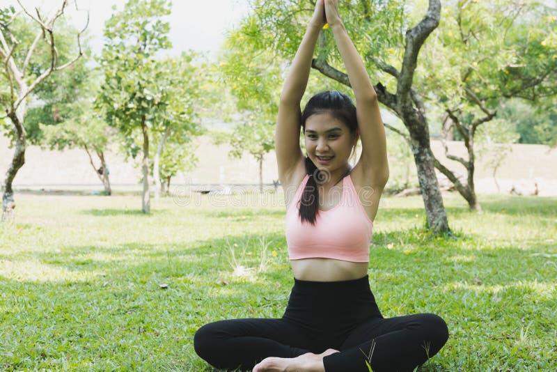 Yoga practicante de la mujer asiática joven al aire libre en parque de la mañana Concentrado imagen de archivo libre de regalías