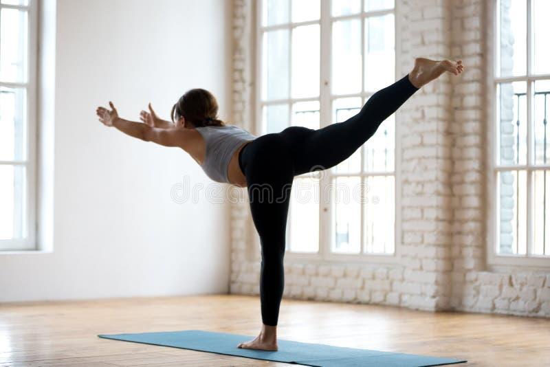Yoga practicante de la mujer atractiva deportiva joven, posición del guerrero tres imagen de archivo