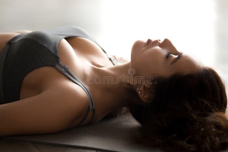 Yoga practicante de la mujer atractiva joven, actitud del cadáver, cierre para arriba imagenes de archivo