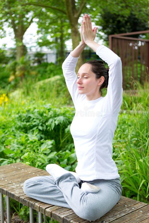 Yoga practicante de la mujer atractiva joven en un parque fotografía de archivo