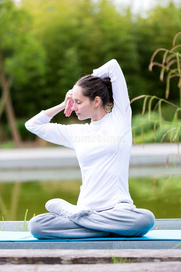 Yoga practicante de la mujer atractiva joven en un parque imágenes de archivo libres de regalías