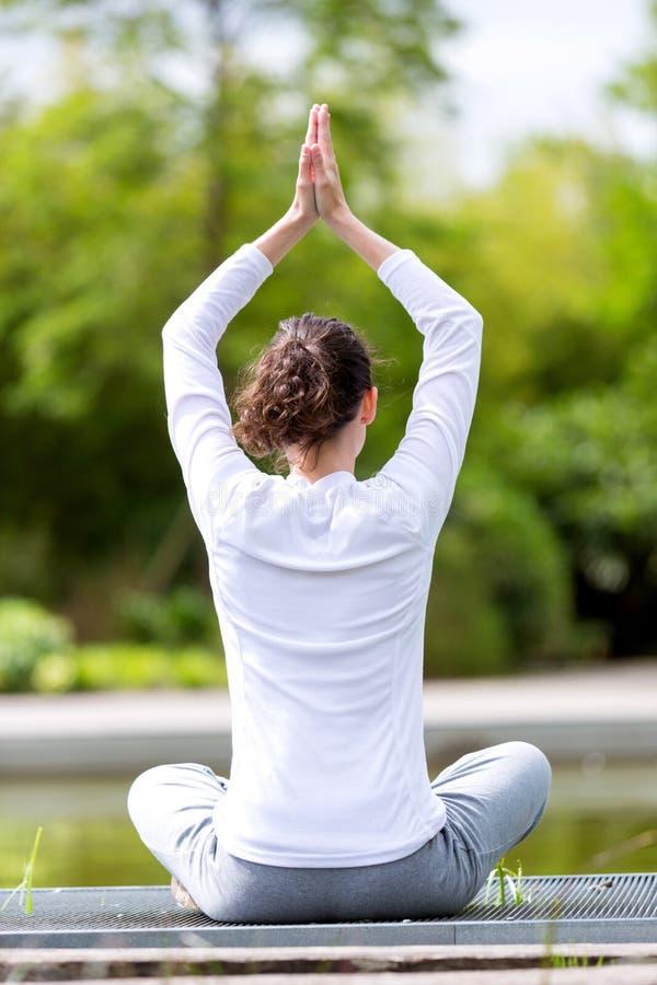 Yoga practicante de la mujer atractiva joven en un parque fotos de archivo