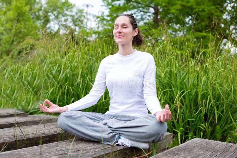 Yoga practicante de la mujer atractiva joven en un parque imagen de archivo libre de regalías
