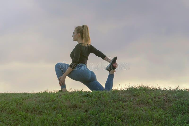 Yoga practicante de la mujer atractiva joven, resolviéndose, entrenamiento al aire libre de la mañana, salida del sol hermosa foto de archivo