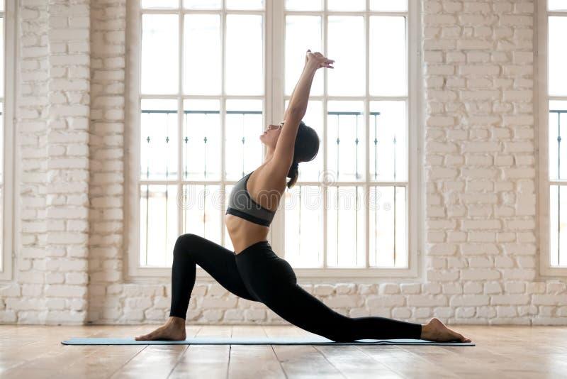 Yoga practicante de la mujer atractiva joven de la yogui, haciendo al jinete e del caballo imagen de archivo
