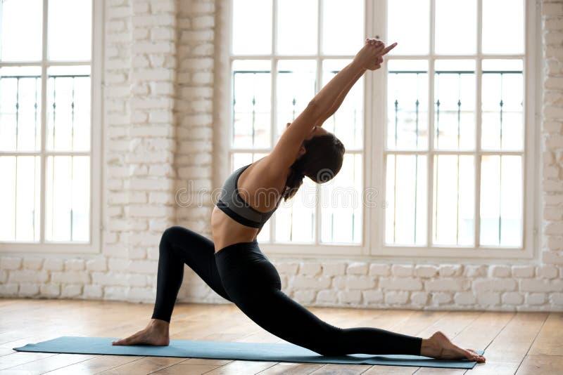 Yoga practicante de la mujer atractiva joven de la yogui, haciendo anjaneyasana imagenes de archivo