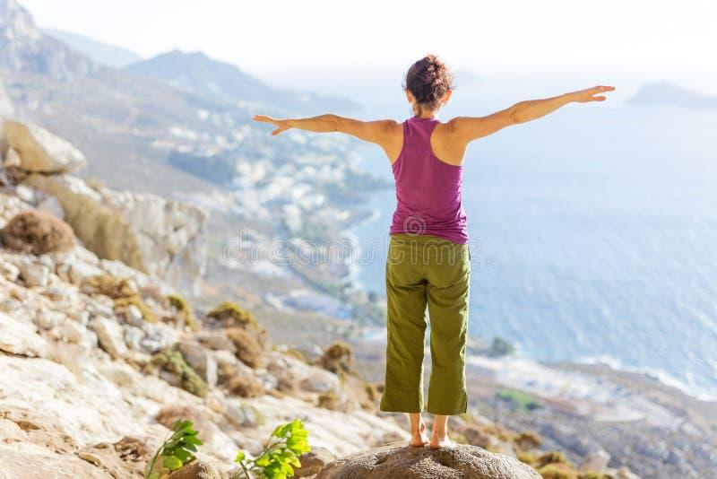 Yoga practicante de la mujer caucásica joven mientras que se coloca en el acantilado en costa de mar fotos de archivo