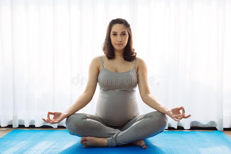 Yoga practicante de la mujer embarazada de los j?venes fotografía de archivo libre de regalías